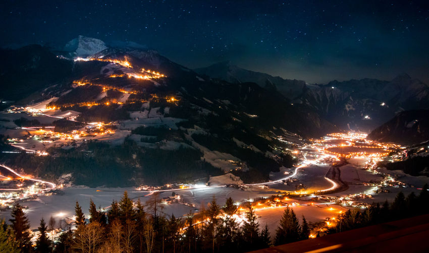 Scenic view of illuminated villages and mountains at night