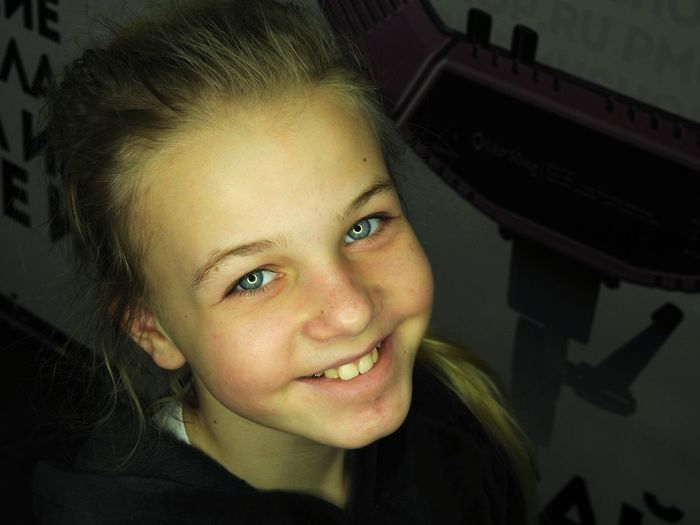Close-up of girl smiling while standing by wall