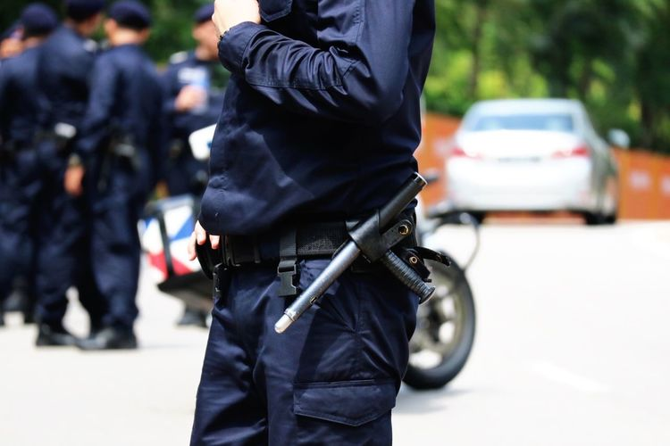 Midsection of police man standing on road