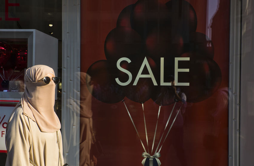A woman wearing a niqab walking in front of a windows display sales on 9th of July 2018 in London, United Kingdom. London sales are also eagerly awaited, and shops will display unbeatable prices. (photo by Lorenzo Grifantini) Oxford Circus Boutique Clothing Store Fashion Female Likeness Human Representation Islam Muslim Outdoors Red Religion Retail  Retail Display Sale Sky Store Window