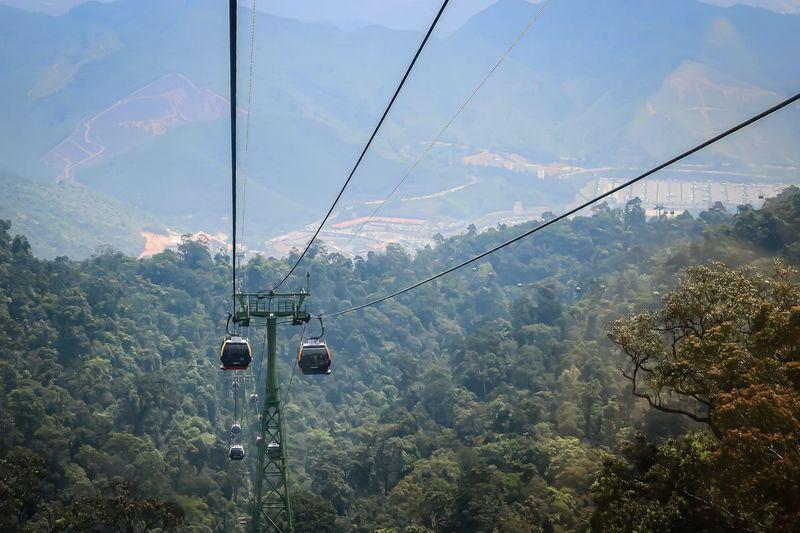 Overhead cable car on mountains against sky