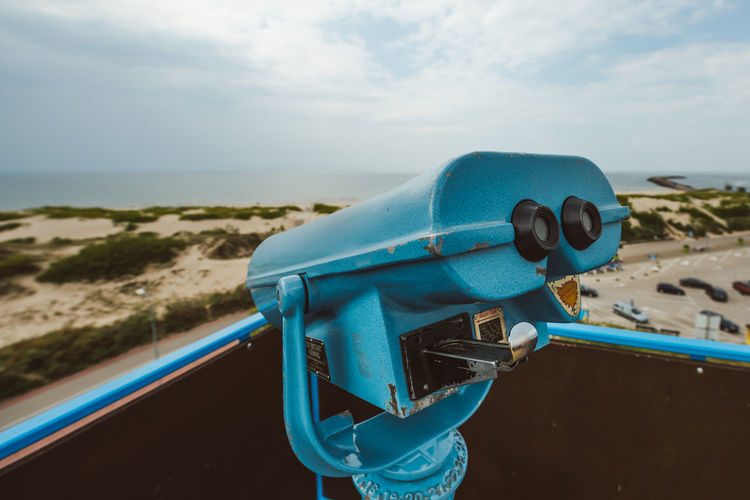 Close-up of coin-operated binoculars against sea
