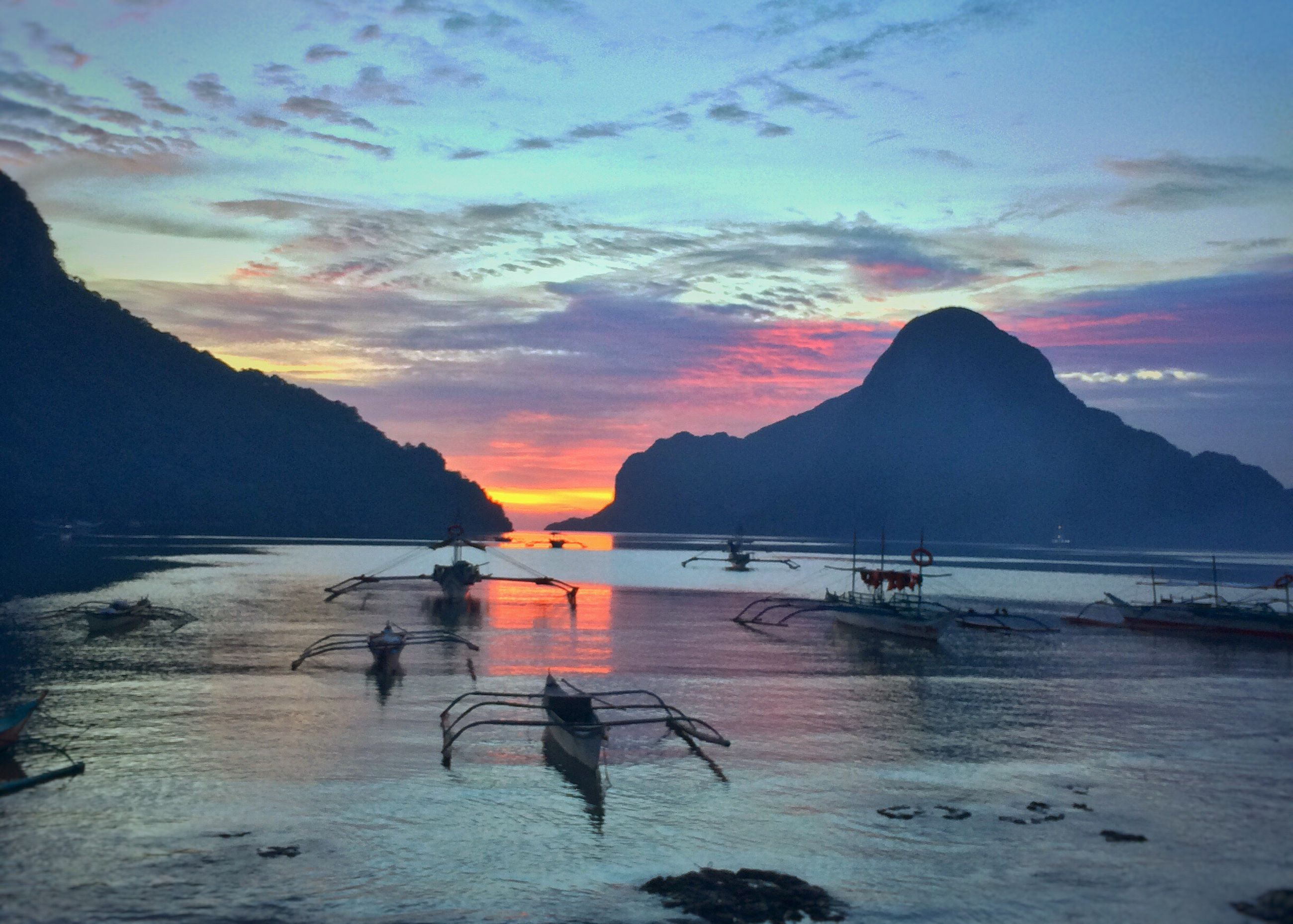 water, mountain, sunset, nautical vessel, scenics, sky, tranquility, tranquil scene, beauty in nature, boat, mountain range, nature, mode of transport, cloud - sky, idyllic, cloud, non-urban scene, outdoors, orange color, remote, calm, majestic, no people, tourism, sailboat, travel destinations, rippled, cloudy