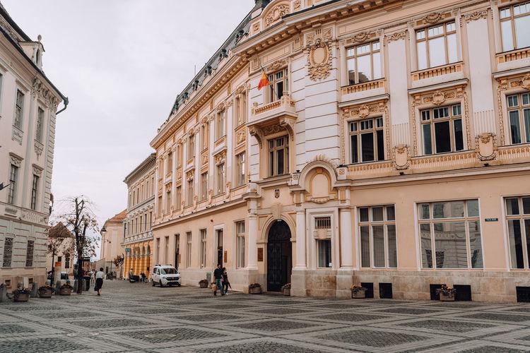 People on street by buildings against sky
