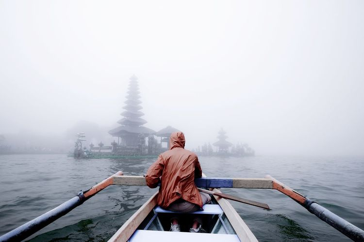 Rear view of man on boat against sky
