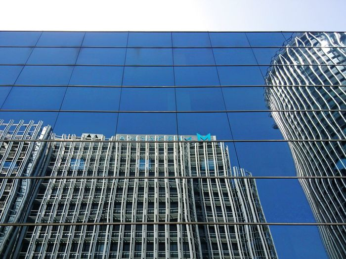 Low angle view of skyscraper against blue sky