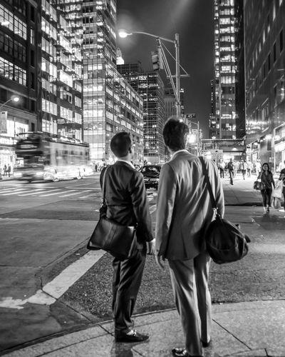 Businessmen Standing On Street Looking At Illuminated Buildings In City