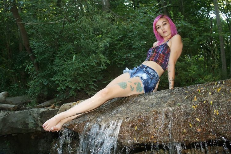 Portrait Of Seductive Woman With Dyed Hair Sitting On Rock In Forest