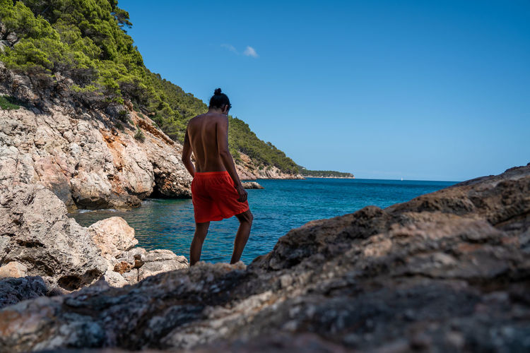 Rear view of man standing on rock by sea against sky