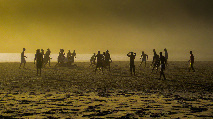 People Playing Soccer At Beach During Sunset