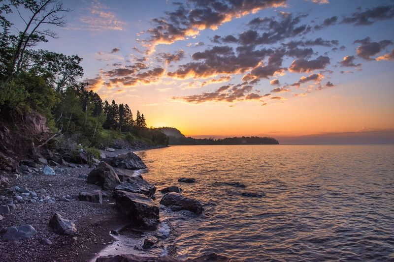 Good Morning Lake Superior Sunset Beauty In Nature Sky Nature Scenics Orange Color Tranquil Scene Tranquility Sea Water Cloud - Sky No People Tree Outdoors Horizon Over Water Day Malephotographerofthemonth Lake Superior Streamzoofamily Beach Beauty In Nature Sunset And Clouds