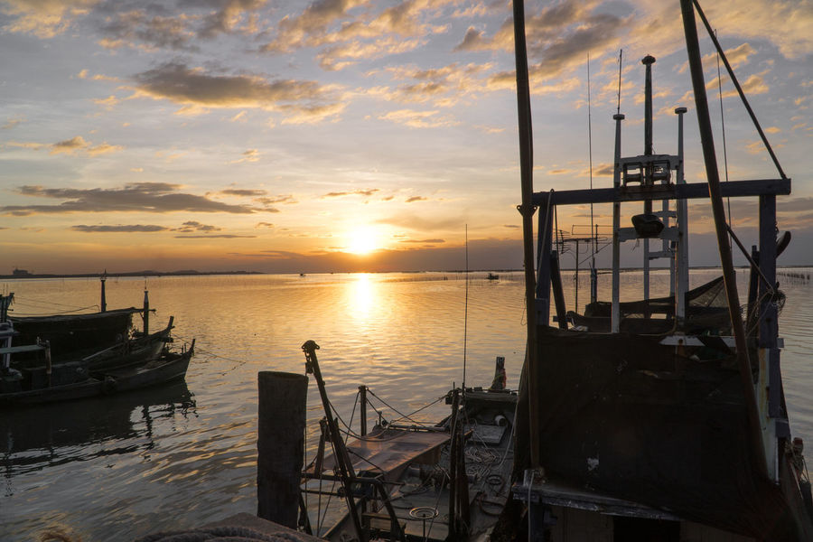 Fishing boats are parked in the the sky and clouds At sunset Fishing Boats Harbor Sky And Clouds Background Feeling Lonely Fishing Boat Outdoors Sea Siluate Sunlight Reflected Sunset