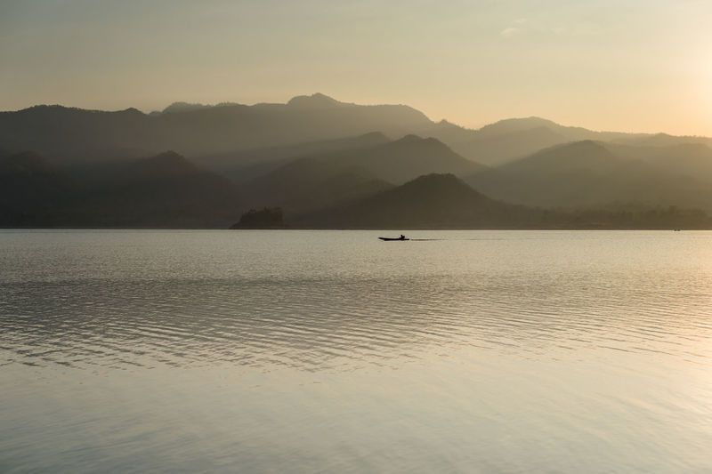 Mountain Beauty In Nature Scenics - Nature Water Tranquil Scene Tranquility Sky Non-urban Scene Mountain Range Idyllic Waterfront Sunset Nature No People Fog Silhouette Sea Outdoors Day