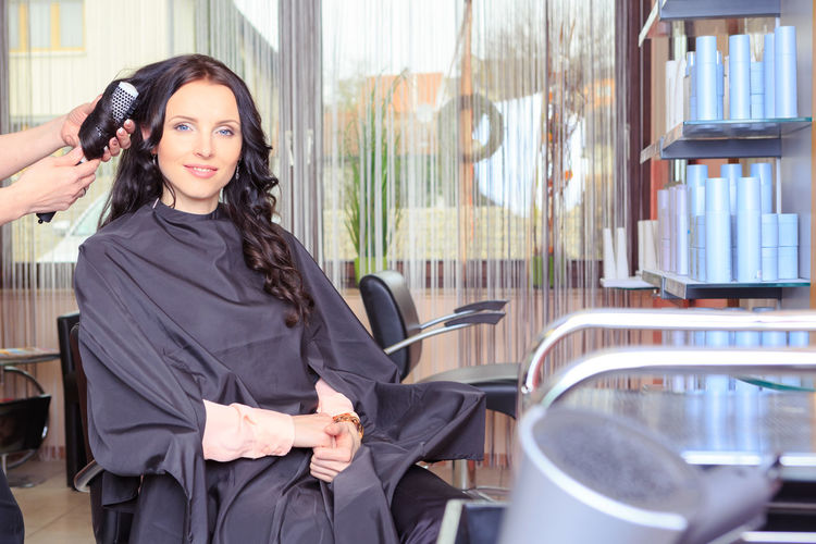 a young woman in beauty or hair salon Adult, Beautiful, Beauty, Care, Caucasian, Client, Comb, Customer, Cut, Cutting, Female, Girl, Hair, Haircut, Hairdresser, Hairdressing, Hairstyle, Happy, Lifestyle, Mirror, Occupation, Person, Professional, Salon, Scissors, Sitting, Smile, Stylist, Treat Young Adult Real People Women Young Women Lifestyles Adult Indoors