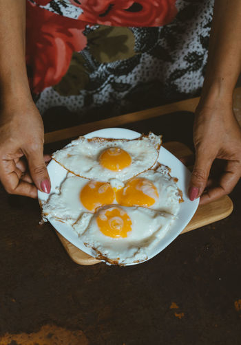 Midsection Of Woman Holding Fried Eggs In Plate On Table