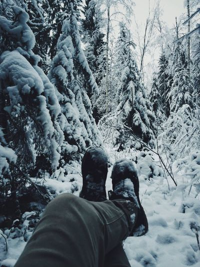 Low section of man with legs crossed at ankle against snow covered trees