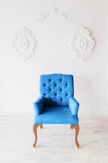 Full frame shot of empty chair against wall at home