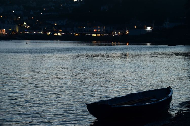 Boat moored on river in city at night