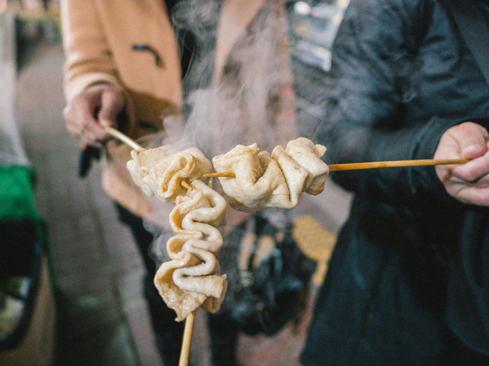 Close-Up Of People Holding Food With Skewers