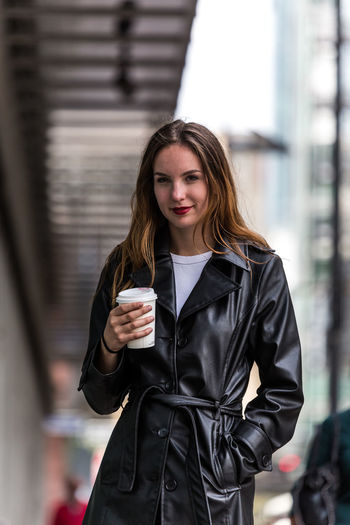 Portrait Of Woman Having Coffee While Standing In City