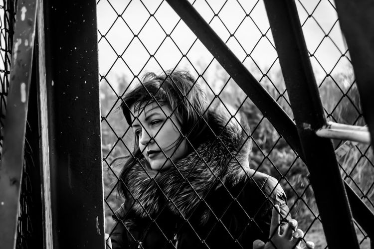 Woman seen through chainlink fence on sunny day