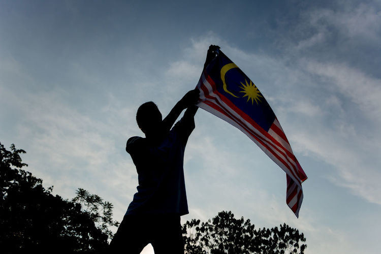 Low angle view of man waving malaysian flag against sky
