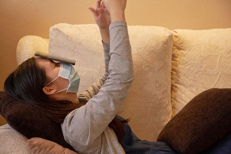Midsection of woman lying on sofa