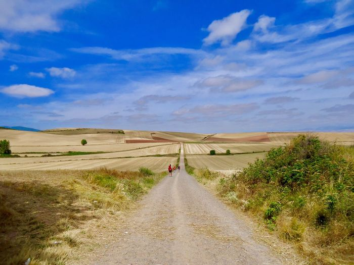 Road Amidst Landscape Against Blue Sky