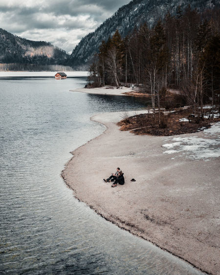 High angle view of couple sitting by lake against trees