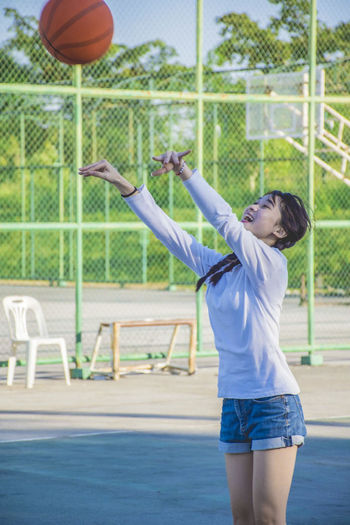 Cute girl playing basketball Three Quarter Length One Person Sport Leisure Activity Casual Clothing Ball Playing Standing Young Adult Human Arm Court Motion Basketball - Sport Fun Day Limb Throwing  Arms Raised Hair Shorts Basketball - Ball Hairstyle Human Limb