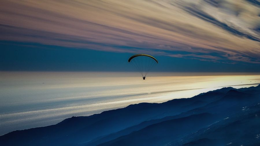Silhouette person paragliding against sky during sunset