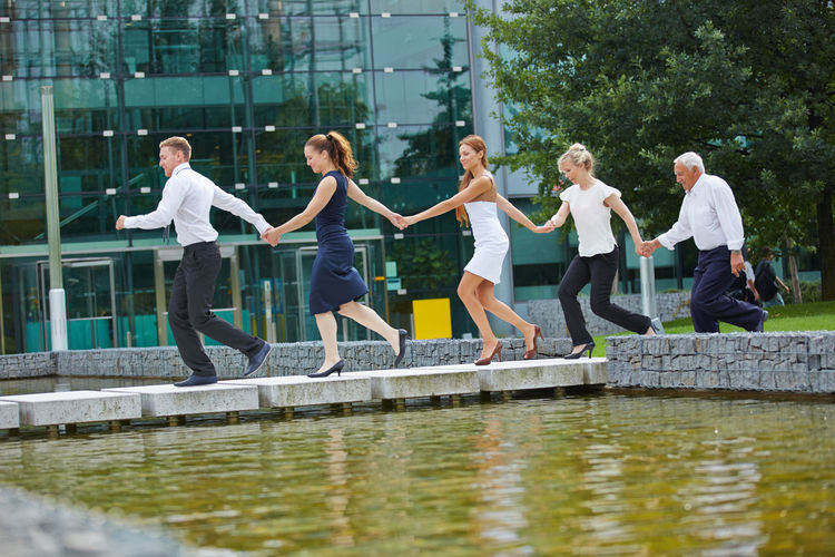 Business Colleagues Holding Hands While Running On Footpath Over Pond