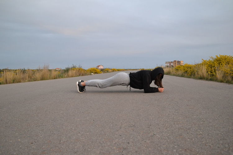Side view of woman exercising on road against sky