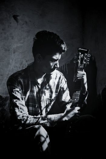 Young man holding guitar while sitting against wall