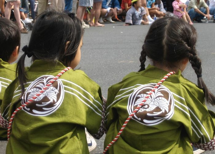 Rear view of girls wearing costume on street during event