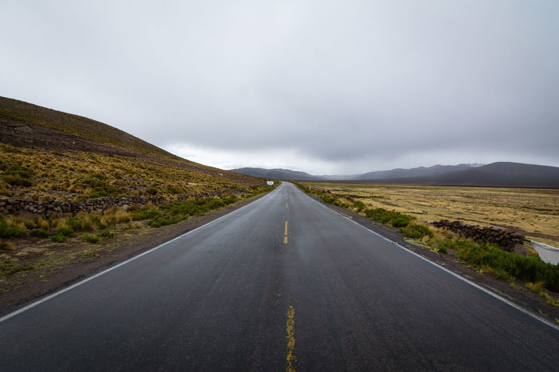 Beauty In Nature Cloud Cloud - Sky Cloudy Country Road Countryside Day Diminishing Perspective Empty Empty Road Landscape Long Mountain Mountain Range Nature Non-urban Scene Remote Road Road Marking Scenics Sky The Way Forward Tranquil Scene Tranquility Vanishing Point