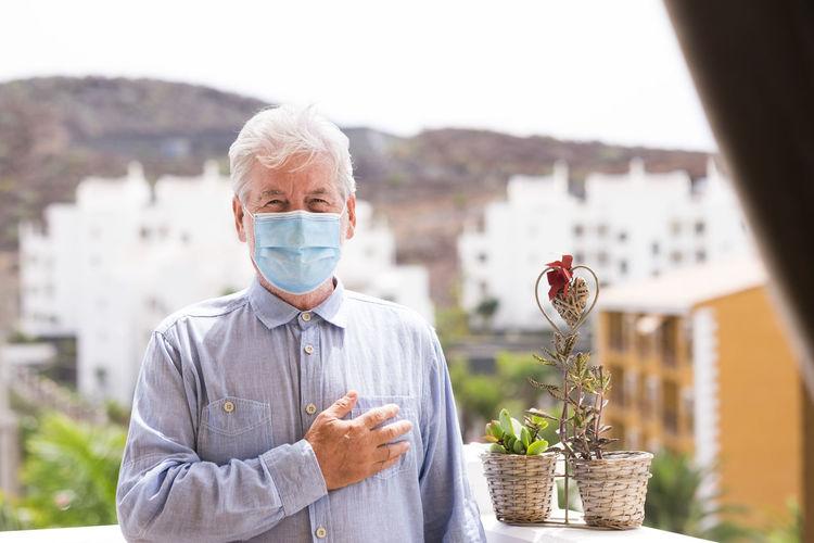 Portrait of senior man wearing mask gesturing against building