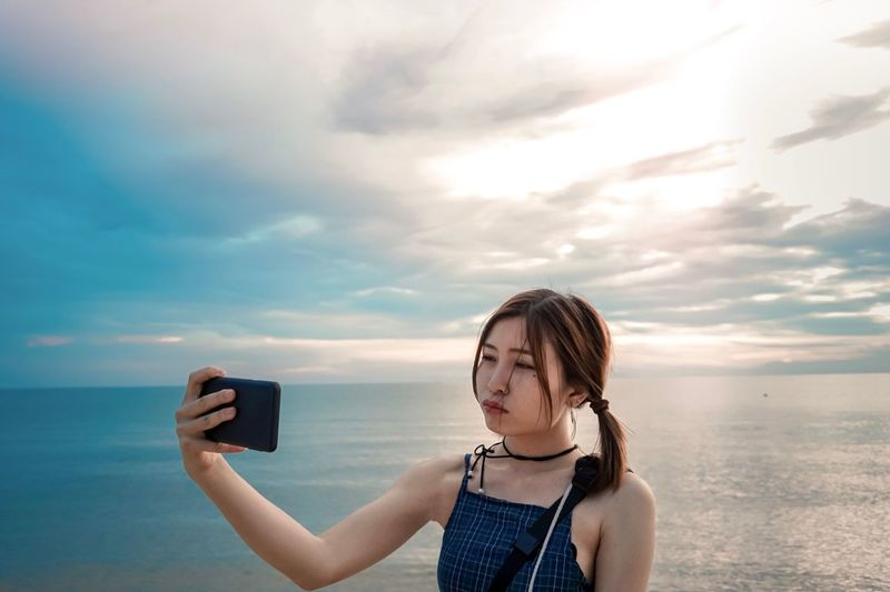 Young Woman Taking Selfie While Standing Against Sky