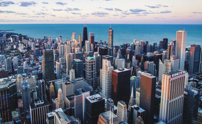 Aerial view of modern buildings by sea against cloudy sky