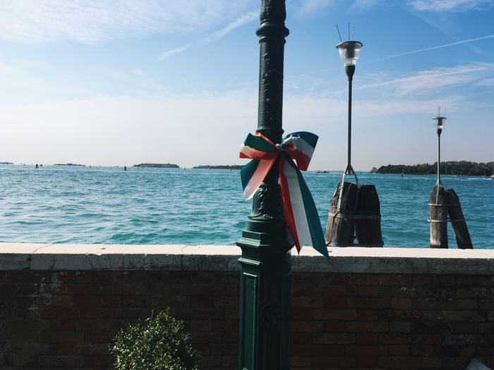 Scenic view of lamppost tied with italian knot against sky and sea