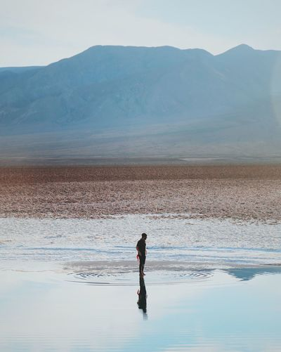 Man standing by reflection in lake against mountain
