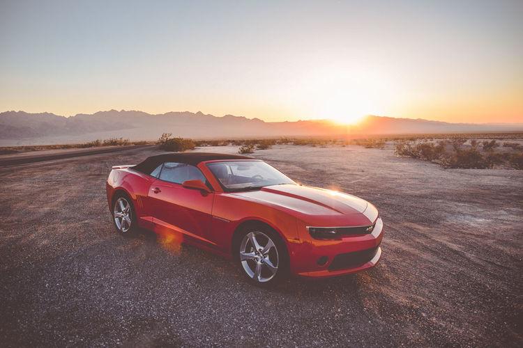 Vintage car on land against sky during sunset