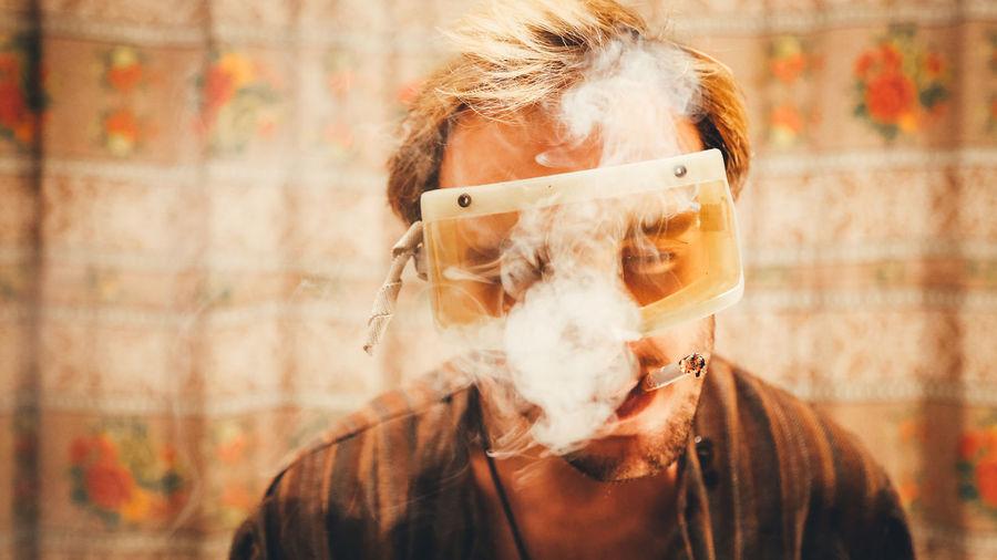 Man wearing protective eyeglasses while smoking cigarette