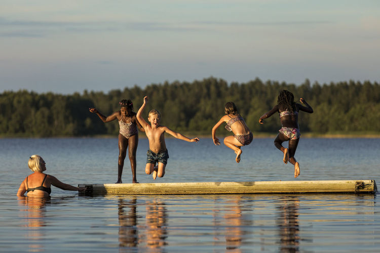 Group of people jumping in lake
