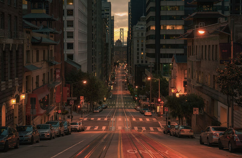 City street amidst buildings during sunset