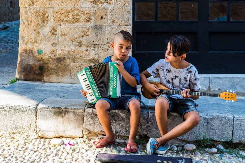 #busker #streetphotography Accordion Adult Bonding Boys Casual Clothing Child Childhood Day Full Length Holding Learning Leisure Activity Outdoors People Playing Real People Sitting Togetherness Two People The Week On EyeEm