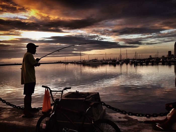 Side View Of Young Man Fishing In Sea Against Cloudy Sky During Sunset