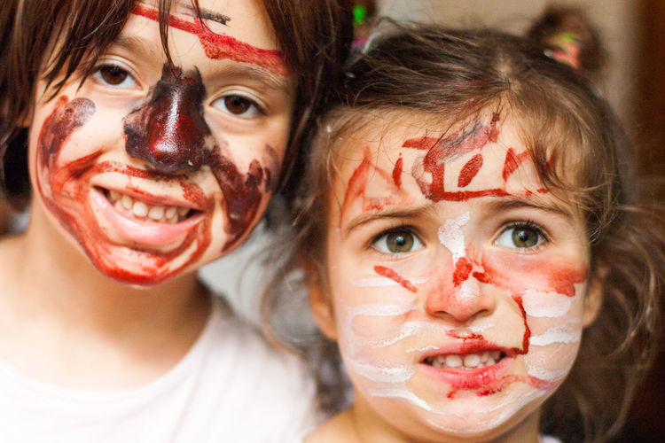 Close-up portrait of sisters with messy face at home