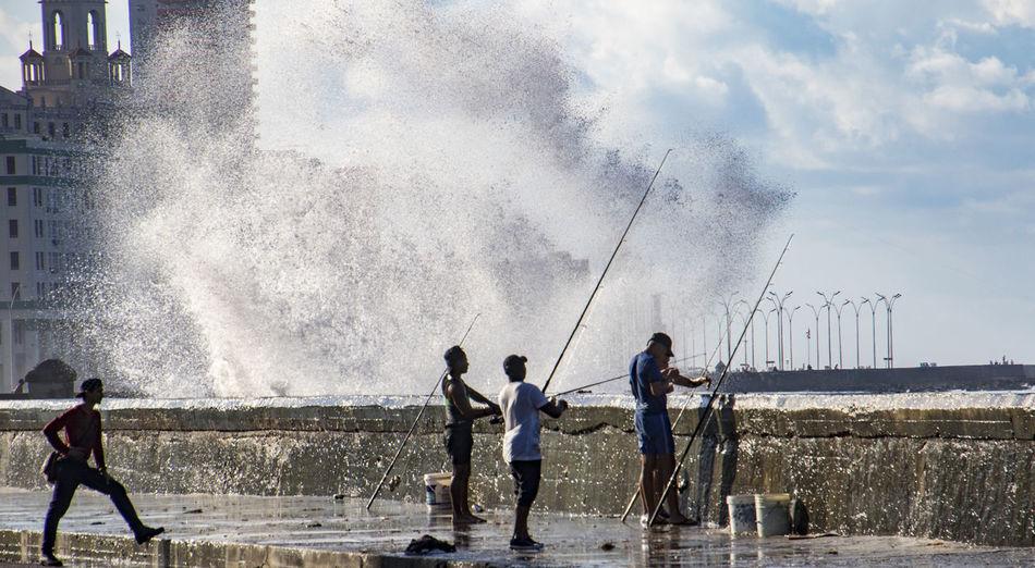 People enjoying in sea against sky