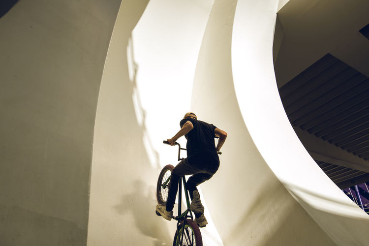 Man riding bicycle on staircase of building